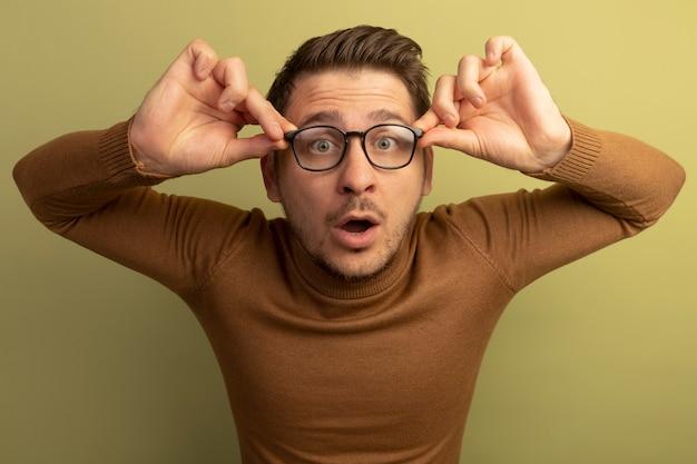 Jovem loiro bonito e impressionado usando e agarrando os óculos