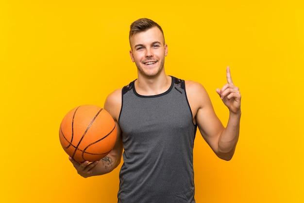 Jovem loiro bonito segurando uma bola de basquete sobre parede amarela isolada apontando uma ótima idéia
