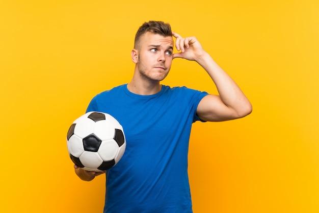 Jovem loiro bonito segurando uma bola de futebol com dúvidas e com a expressão do rosto confuso
