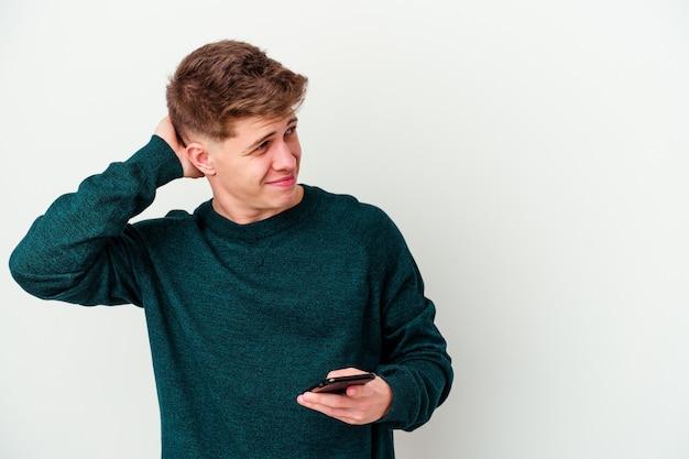 Jovem loiro branco usando um telefone isolado na parede branca, tocando a nuca, pensando e fazendo uma escolha