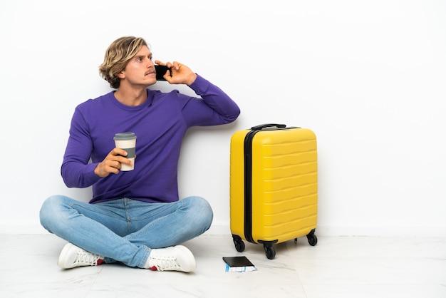 Jovem loiro com uma mala sentada no chão segurando um café para levar e um celular