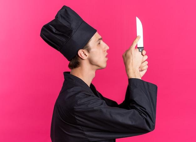 Jovem loiro concentrado cozinheiro masculino com uniforme de chef e boné em pé na vista de perfil, olhando e tocando a faca com o dedo
