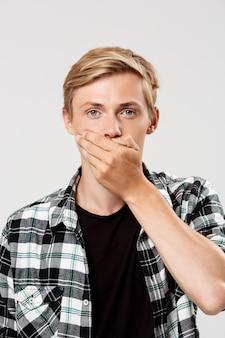 Jovem loiro confiante bonito vestindo camisa xadrez casual, cobrindo a boca com a mão, na parede cinza