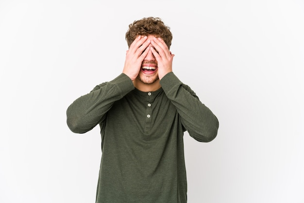 Jovem loiro encaracolado homem caucasiano de cabelo encaracolado isolado cobre os olhos com as mãos, amplamente à espera de uma surpresa.