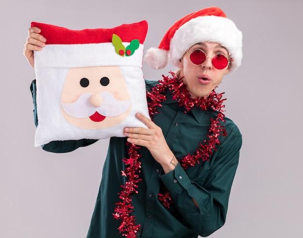 Jovem loiro impressionado com chapéu de papai noel e óculos com guirlanda de ouropel no pescoço, segurando uma almofada de papai noel, olhando para a câmera isolada no fundo branco