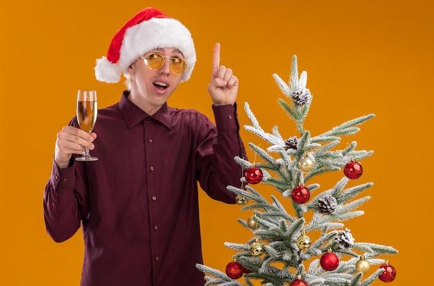 Jovem loiro impressionado com chapéu de papai noel e óculos em pé perto da árvore de natal decorada segurando uma taça de champanhe, olhando para o lado apontando para cima isolado em um fundo laranja