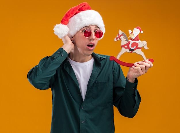 Jovem loiro impressionado com chapéu de papai noel e óculos segurando o papai noel na estatueta do cavalo de balanço, olhando para a câmera, mantendo a mão na cabeça isolada em fundo laranja