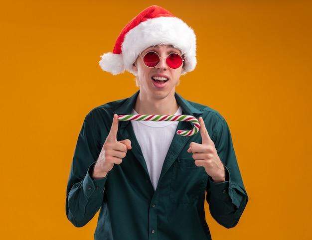Jovem loiro impressionado com chapéu de papai noel e óculos segurando uma bengala de natal horizontalmente olhando para a câmera isolada em fundo laranja