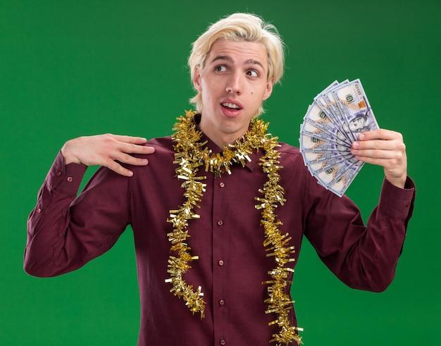Jovem loiro impressionado de óculos com guirlanda de ouropel no pescoço, segurando dinheiro tocando o ombro, olhando para o lado isolado no fundo verde