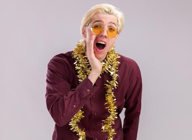 Jovem loiro impressionado usando óculos com guirlandas de ouropel no pescoço, olhando para a câmera, mantendo a mão perto da boca, chamando alguém isolado no fundo branco com espaço de cópia