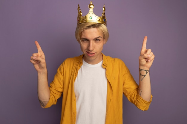 Jovem loiro impressionado vestindo camiseta amarela e a coroa apontando para cima isolada no roxo