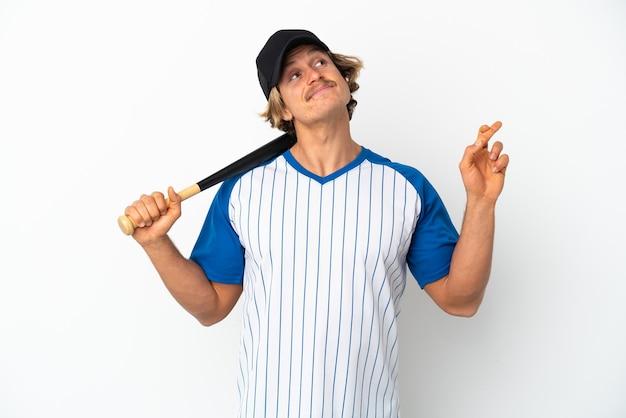 Jovem loiro jogando beisebol isolado no fundo branco, cruzando os dedos e desejando o melhor