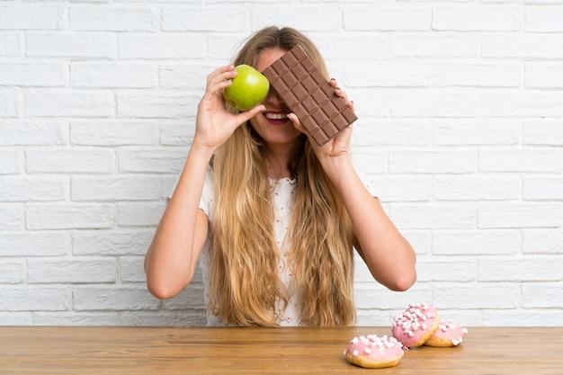 Jovem, loiro, mulher, com, chocolat, e, um, maçã