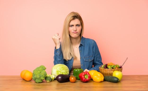 Jovem, loiro, mulher, com, muitos, legumes, com, zangado, gesto
