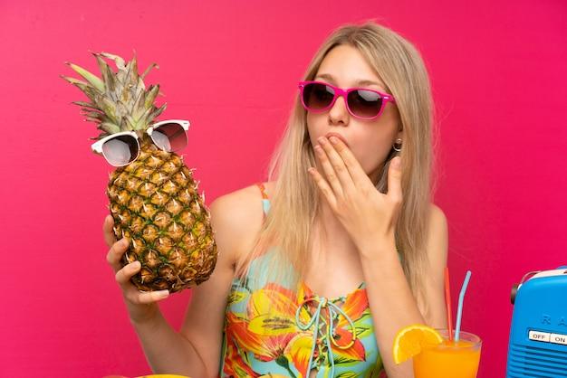 Jovem, loiro, mulher, em, swimsuit, segurando, um, abacaxi, com, óculos de sol