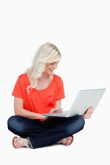 Jovem, loiro, mulher senta-se, cross-legged, com, dela, laptop, ligado, dela, perna