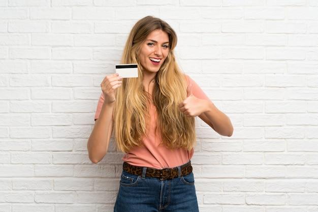 Jovem, loiro, mulher, sobre, branca, parede tijolo, segurando, um, cartão crédito