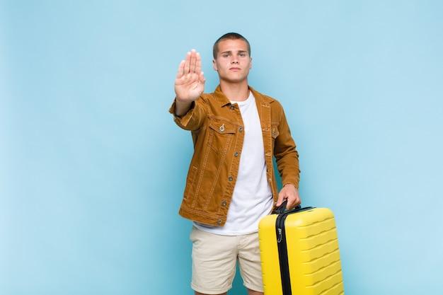 Jovem loiro parecendo sério, severo, descontente e irritado, mostrando a palma da mão aberta fazendo gesto de pare