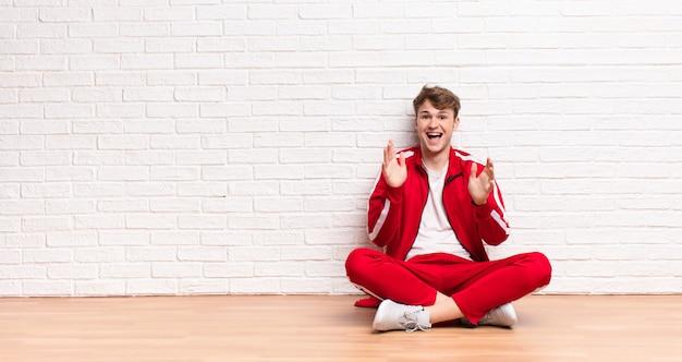 Jovem loiro se sentindo chocado e animado, rindo, surpreso e feliz por causa de uma surpresa inesperada sentado no chão