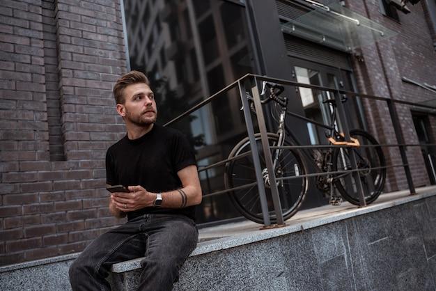 Jovem loiro sentado no parapeito da parede de pedra perto de sua bicicleta de estrada enquanto envia mensagens, gosta ou publica nas redes sociais, parecendo pensativo à distância, usando jeans e camiseta pretos