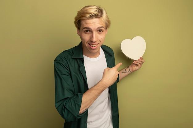 Jovem loiro sorridente vestindo uma camiseta verde segurando e apontando para uma caixa em formato de coração