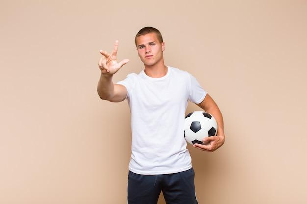 Jovem loiro sorrindo e parecendo amigável, mostrando o número três ou o terceiro com a mão para a frente, em contagem regressiva