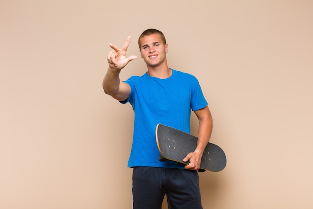 Jovem loiro sorrindo e parecendo amigável, mostrando o número três ou terceiro com a mão para a frente, em contagem regressiva
