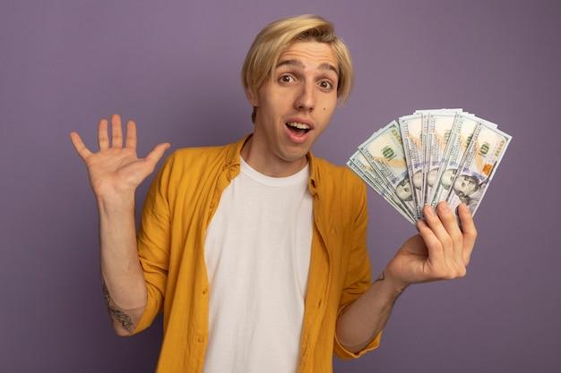 Jovem loiro surpreso com uma camiseta amarela segurando dinheiro e levantando a mão isolada no roxo