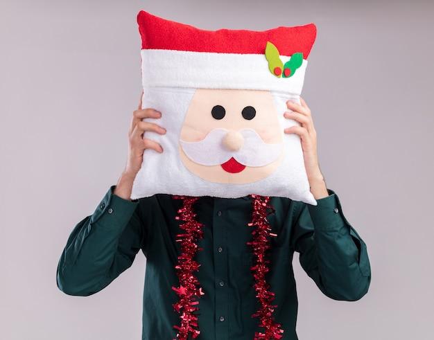 Jovem loiro usando chapéu de papai noel e óculos com guirlanda de ouropel em volta do pescoço segurando uma almofada de papai noel cobrindo o rosto com ela isolada no fundo branco