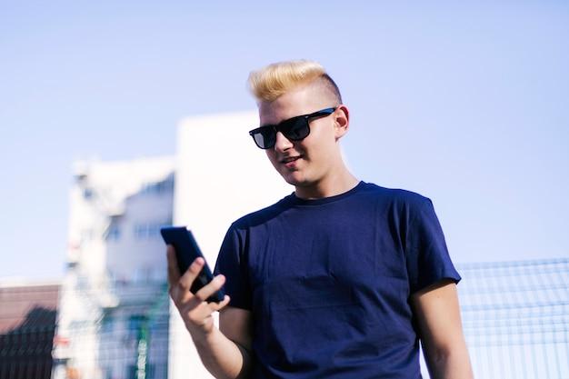 Jovem loiro usando um telefone celular na rua