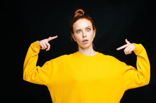 Jovem louca e alegre em um suéter amarelo brincando e mostrando a língua no fundo preto isolado