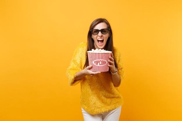 Jovem louca em óculos 3d imax assistindo filme filme gritando segurando balde de pipoca isolado em fundo amarelo brilhante. emoções sinceras de pessoas no conceito de estilo de vida de cinema. área de publicidade.