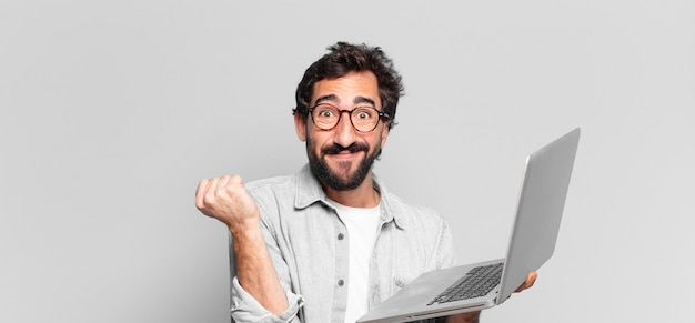 Jovem louco barbudo. celebrando um triunfo como um vencedor. conceito de laptop