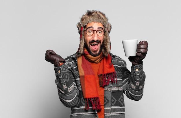 Jovem louco barbudo celebrando um triunfo como um vencedor e vestindo roupas de inverno