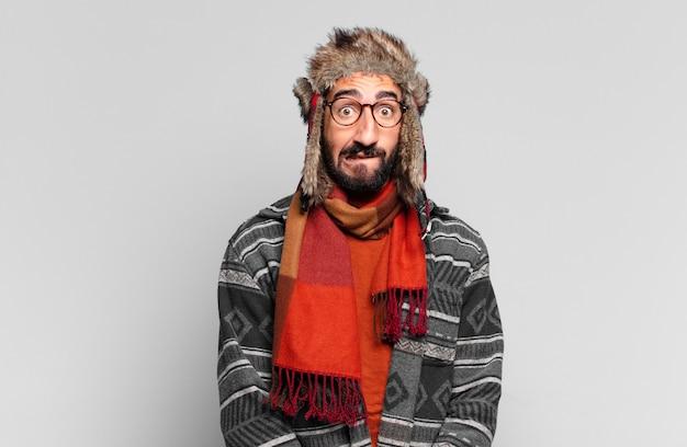 Jovem louco barbudo com expressão chocada e vestindo roupas de inverno
