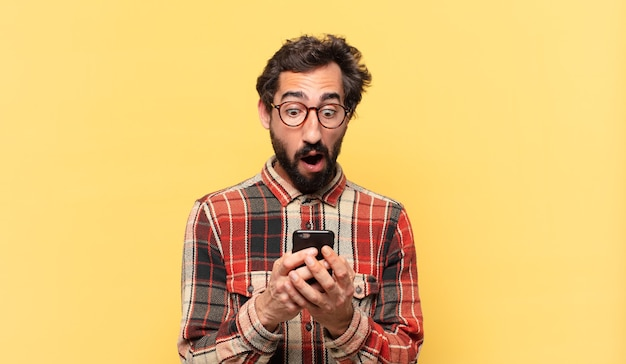 Jovem louco barbudo com expressão de medo e segurando um telefone