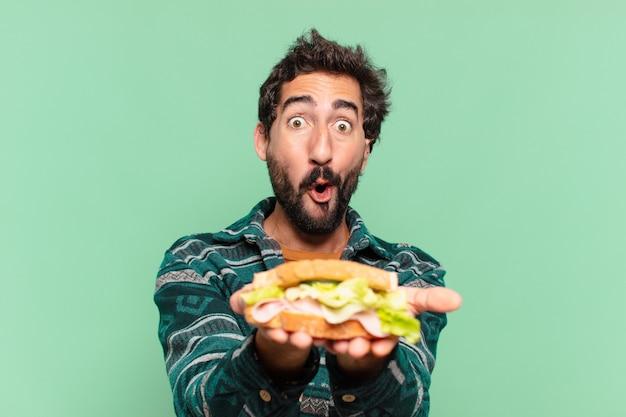 Jovem louco barbudo com expressão de surpresa e segurando um sanduíche