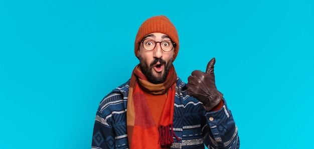 Jovem louco barbudo com expressão feliz e surpresa e vestindo roupas de inverno