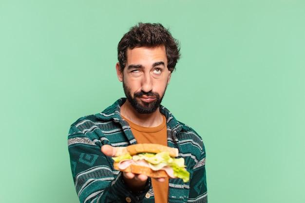 Jovem louco barbudo com expressão triste e segurando um sanduíche