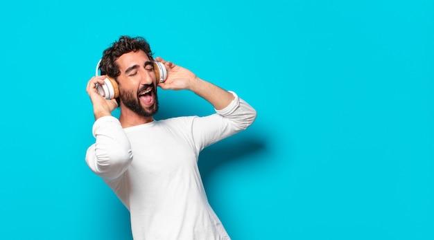 Jovem louco barbudo com fones de ouvido ouvindo música Foto Premium