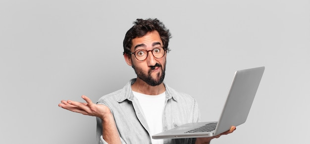 Jovem louco barbudo com medo ou expressão confusa. conceito de laptop