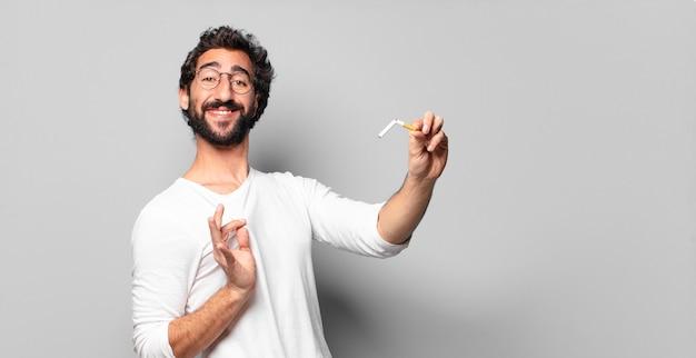 Jovem louco barbudo com um cigarro. nenhum conceito de fumar.
