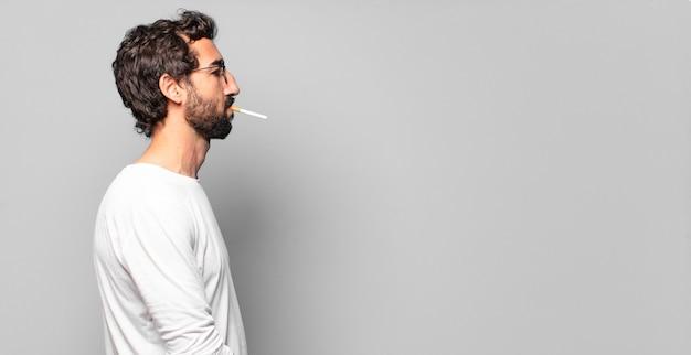 Jovem louco barbudo com um cigarro.