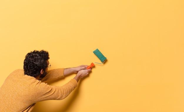 Jovem louco barbudo com um rolo de pintura pintando e mudando a cor da parede