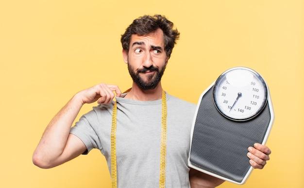 Jovem louco barbudo com uma expressão de medo em dieta e segurando uma balança leve