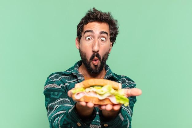 Jovem louco barbudo com uma expressão feliz e segurando um sanduíche