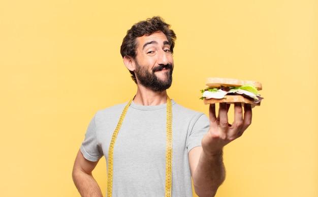 Jovem louco barbudo com uma expressão feliz em dieta e segurando um sanduíche