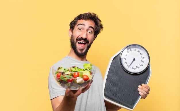 Jovem louco barbudo com uma expressão feliz em dieta e segurando uma balança e uma salada