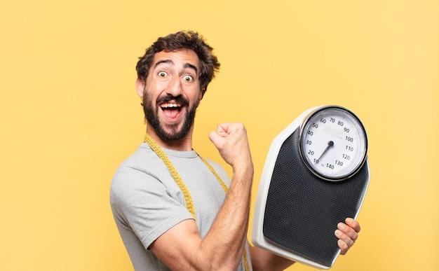 Jovem louco barbudo com uma expressão feliz em dieta e segurando uma balança elegante