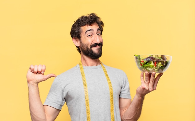 Jovem louco barbudo com uma expressão feliz em dieta e segurando uma salada